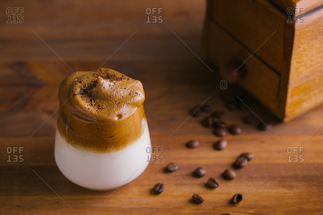 Whipped coffee Dalgona coffee in cold milk placed near vintage coffee grinder and coffee beans on wooden table surface