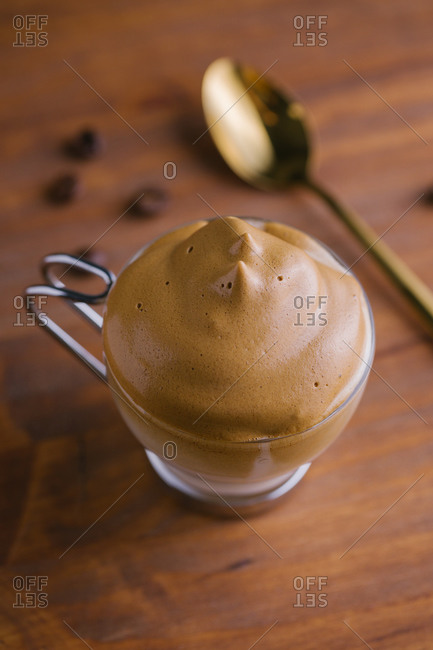 From above whipped coffee Dalgona coffee in cold milk placed near coffee beans and golden teaspoon on wooden table surface