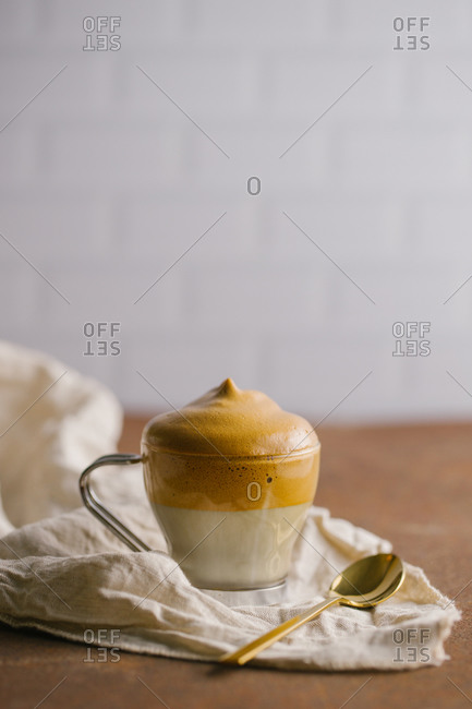 Whipped coffee Dalgona coffee in cold milk placed on a white napkin near golden teaspoon on wooden table surface