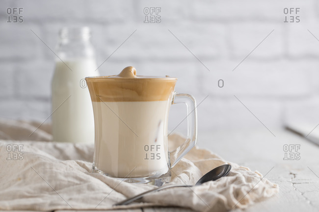 Cold homemade Dalgona beverage with whipped coffee placed on wooden table with bottle of milk and teaspoon