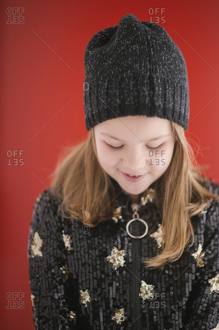Cheerful child with toothy smile in warm black jersey and knitted cap looking down while standing on red background
