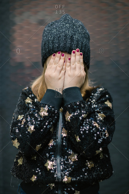 Little anonymous child in knitted cap and warm jacket with manicure on hands covering face while standing outdoors
