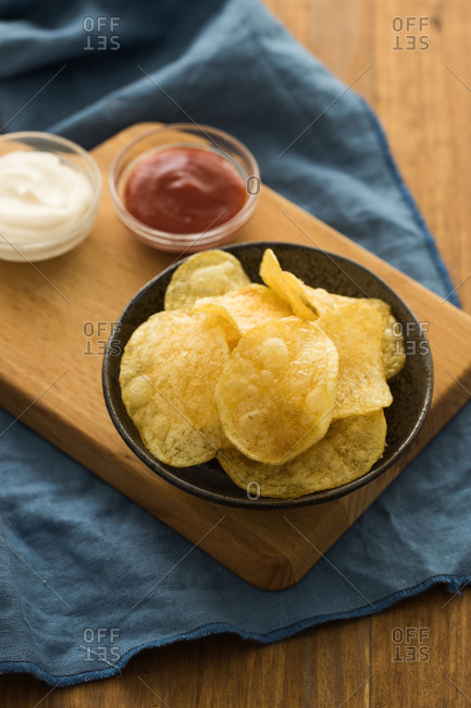 From above yummy potato chips placed on cutting board with ketchup and sour cream