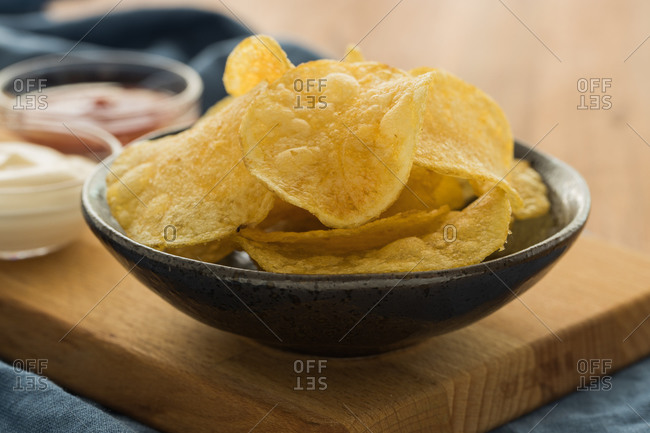 Yummy potato chips placed on cutting board with ketchup and sour cream