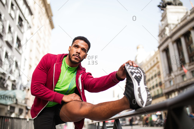 Young man stretching legs in the street
