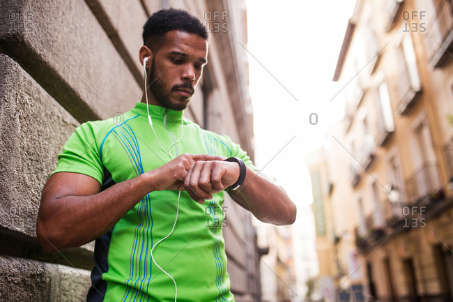 Young man checking his watch in the street