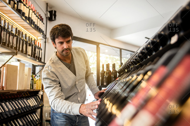 Adult stylish man looking for certain bottle of wine looking through shelf in wine house market.
