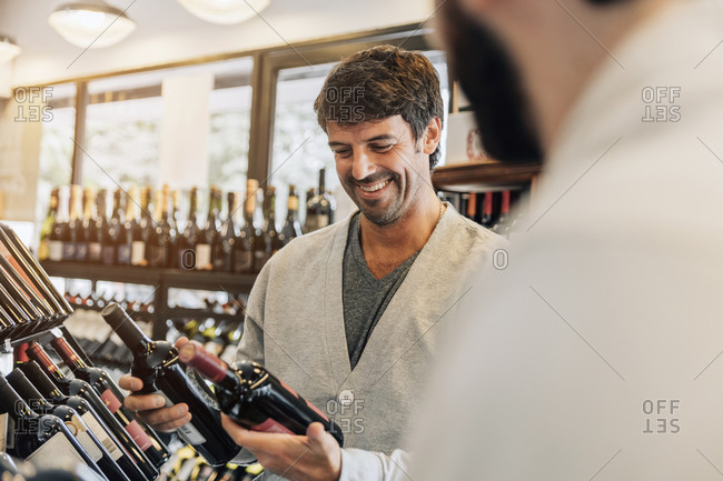 Mid adult man choosing a wine at the supermarket