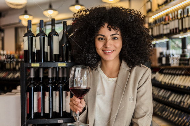 Trendy curly woman holding glass of red wine and smiling at camera in wine market.
