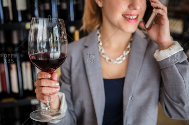 Crop shot of elegant woman in jacket having phone call while tasting wine in vintage house.