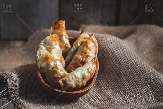 From above of traditional Spanish homemade turnovers served in bowl on rustic wooden table