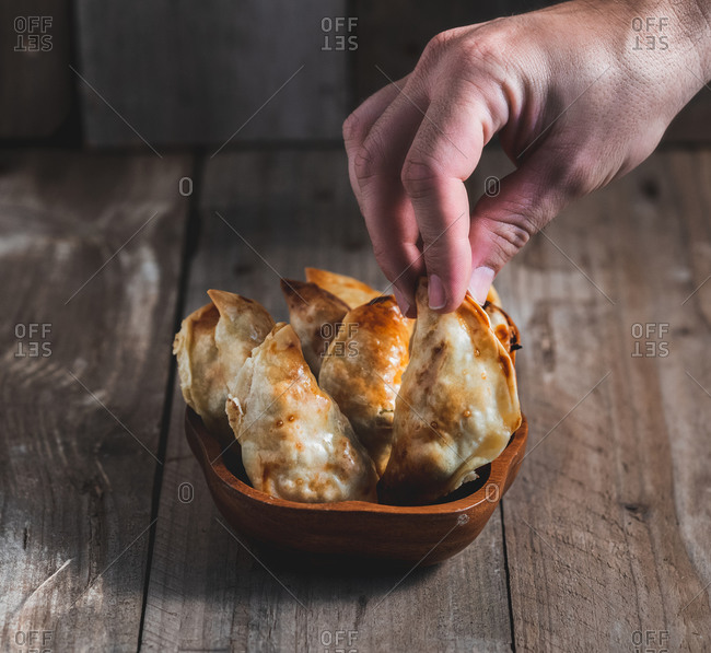 Unrecognizable man picking up a traditional Spanish homemade turnovers served in bowl on rustic wooden table