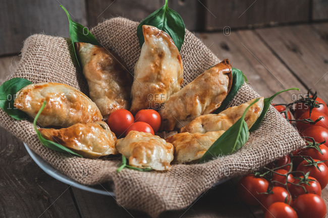 From above of traditional Spanish homemade turnovers served in bowl on rustic wooden table with fresh spinach and tomatoes