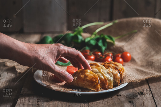 Unrecognizable man picking up a traditional Spanish homemade turnovers served in dish on rustic wooden table with fresh spinach and tomatoes