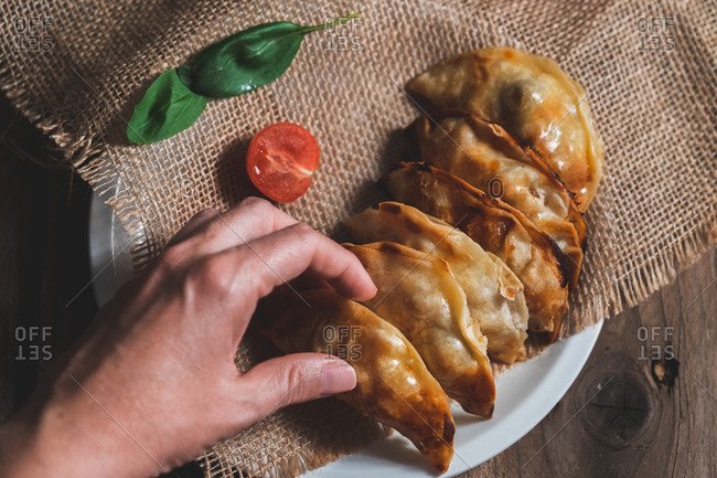 From above unrecognizable man picking up a traditional Spanish homemade turnovers served in bowl on rustic wooden table with fresh spinach and tomatoes