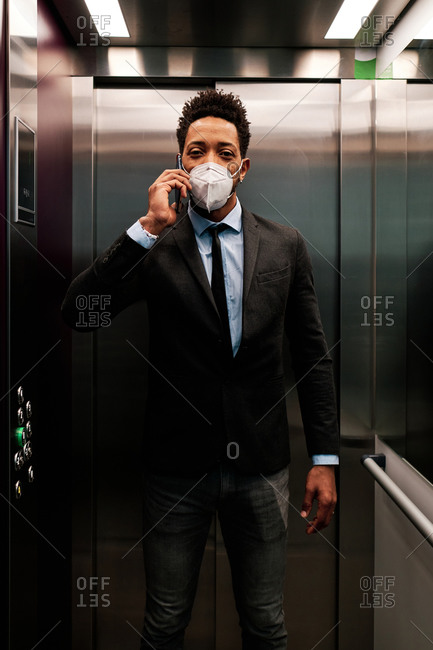 Busy African American male entrepreneur wearing protective respirator during coronavirus epidemic standing in modern elevator while talking on smartphone and looking at camera