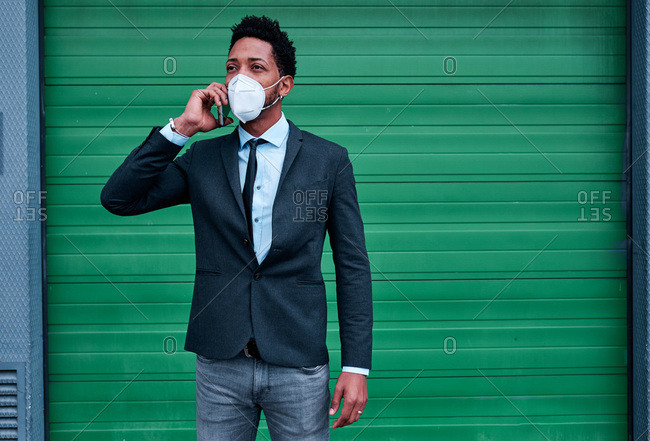 Confident black male entrepreneur in classy suit and protective mask speaking on mobile phone while standing on city street during coronavirus epidemic and looking away