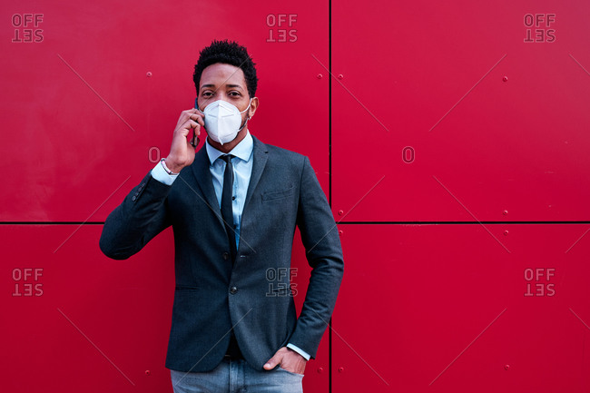 Confident black male entrepreneur in classy suit and protective mask speaking on mobile phone while standing on city street during coronavirus epidemic and looking at camera