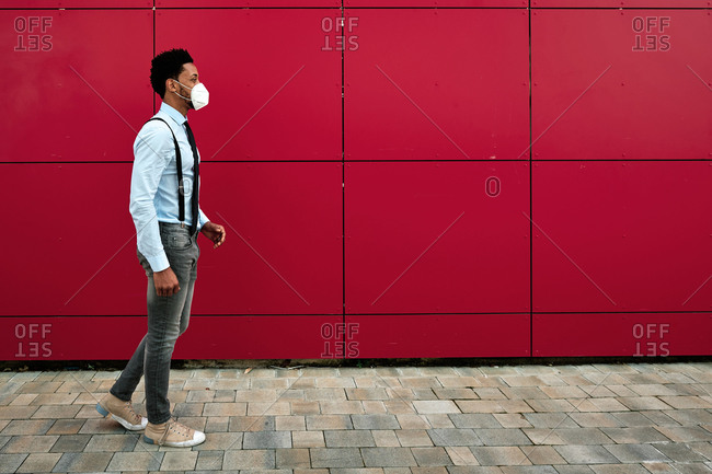 Side view of ethnic male in smart casual style strolling in respirator along sidewalk while spending weekend in city during COVID 19 pandemic