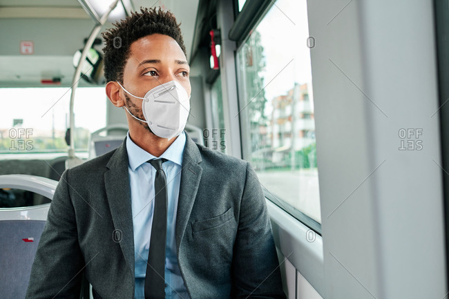 African American businessman wearing formal suit and protective mask sitting on passenger seat in public transport and looking out of window during coronavirus outbreak