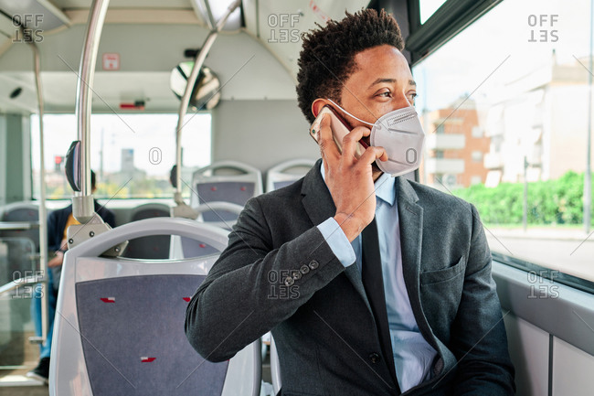 African American businessman wearing formal suit and protective mask sitting on passenger seat in public transport and talking smartphone