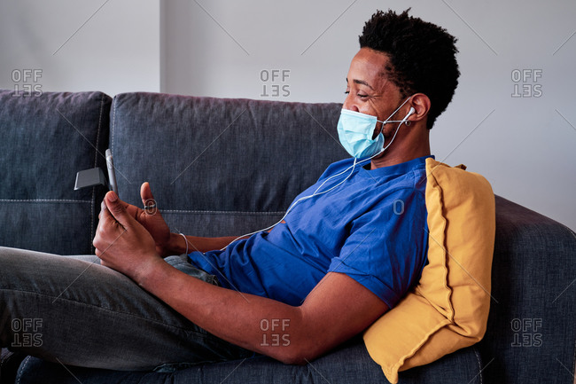 Side view of happy African American male in casual wear and surgical mask speaking on video call via tablet and waving hand while relaxing on sofa at home during quarantine