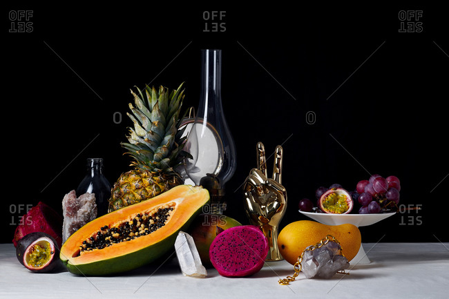 Still life with tropical fruits, kerosene lamp, gems and objects