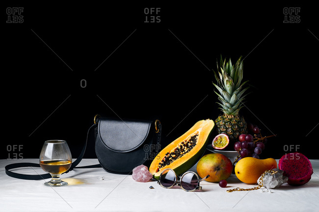 Still life with tropical fruits, gems, black leather bag and various objects