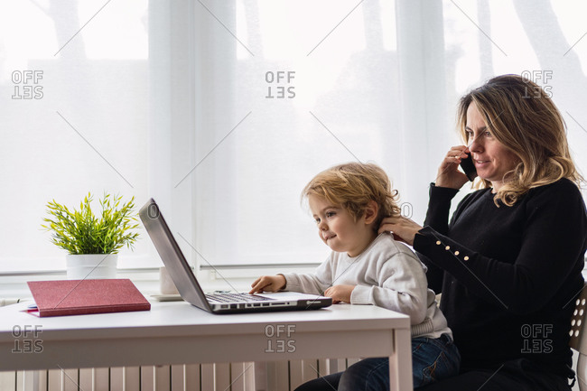 Side view of female remote employee holding curious little child on knees while sitting at table and working with laptop at home