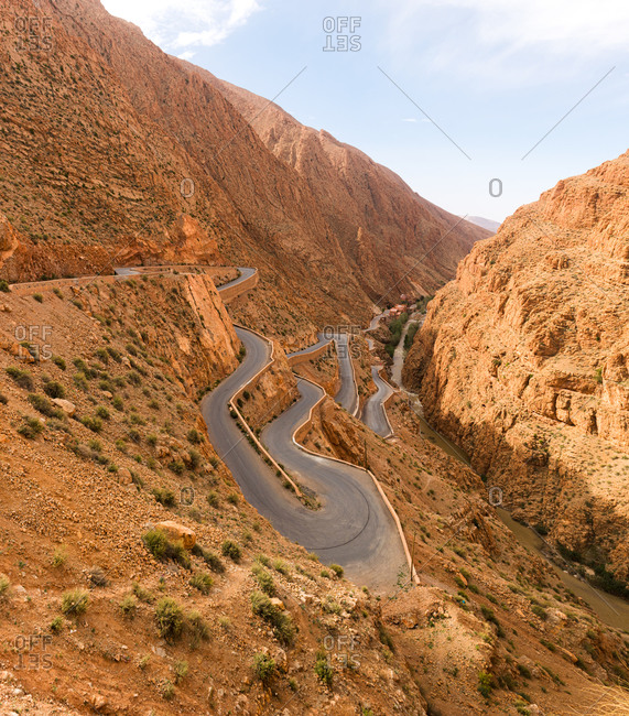 From above of majestic landscape of narrow winding roadway going between rough rocks against blue sky
