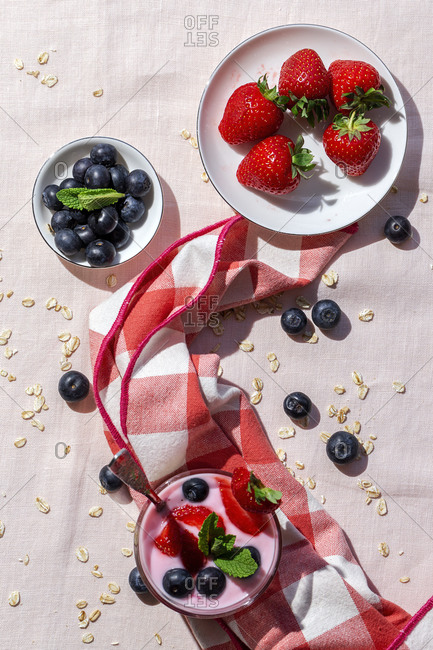 Homemade yogurt with strawberries, blueberries and cereals from above with pink tablecloth and sunlight, Healthy food concept, Vegan food