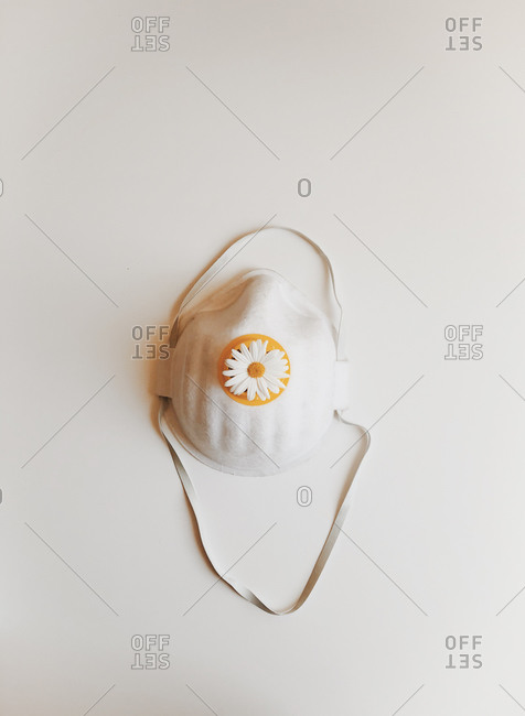 From above of facial protection mask placed on white background isolated as symbol of protection against coronavirus pandemic and other infections