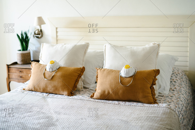 Comfortable bed with pair of facial protection respirator masks placed on soft brown pillows as symbol of protection against coronavirus
