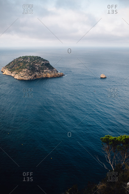 Aerial view of rocky coastline with islet in the middle of the sea close to sea bay with calm blue water against cloudy sky and horizon in light haze at daytime