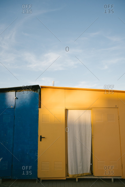 Shabby weathered yellow and blue metallic houses located on pavement in urban area during sunny summer day with clear blue sky