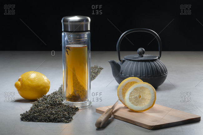 Aromatic beverage in glass mug and teapot arranged with lemons and heaps of dried tea leaves on table on black background