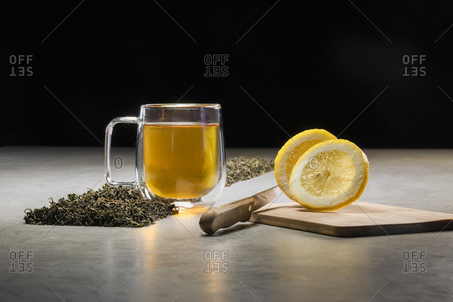Aromatic beverage in glass mug arranged with lemons and heaps of dried tea leaves on table on black background