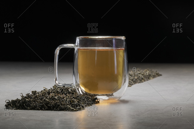 Aromatic beverage in glass mug arranged with heaps of dried tea leaves on table on black background