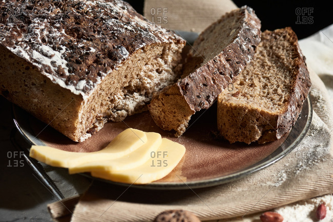 Freshly baked homemade wholegrain bread in baking form placed on table with nuts and pieces of cheese on a rustic plate