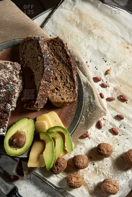 Top view of fresh sliced wholegrain bread served with avocado and cheese for healthy nutrient breakfast on kitchen table