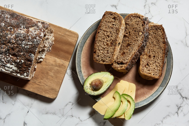 Top view of fresh sliced wholegrain bread served with avocado and cheese for healthy nutrient breakfast on kitchen marble table