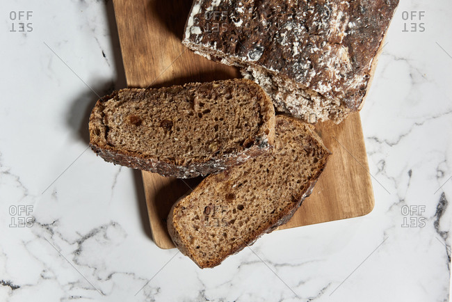 Top view of delicious healthy wholegrain rye bread loaf with slices served on wooden cutting board on marble table