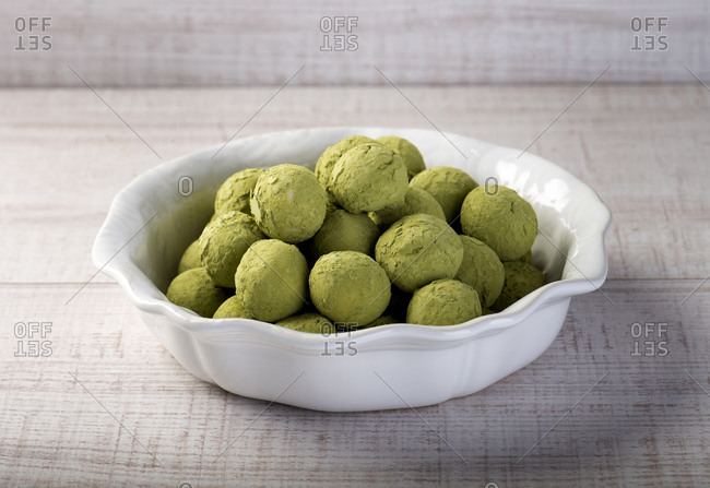 High angle of white ceramic bowl with yummy homemade green truffles made with matcha tea powder placed on wooden counter