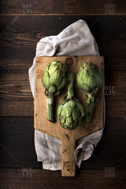 Top view of fresh green artichokes arranged on wooden cutting board on rustic lumber table