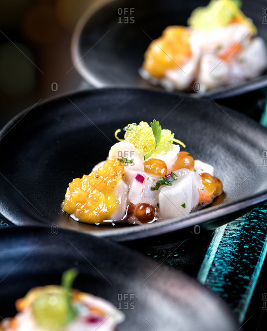 Sophisticated corvina fish ceviche served with sweet potato cream and tobiko or flying fish caviar in modern restaurant