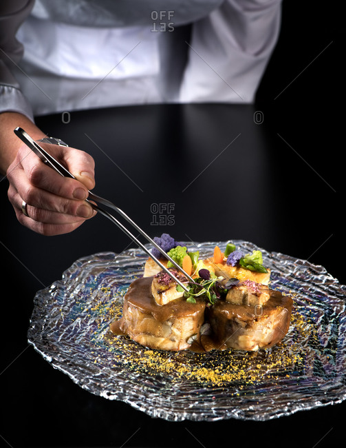 Crop anonymous chef with tongs garnishing gourmet organic sirloin steak with potato strudel and boletus confit in wine sauce in modern haute cuisine restaurant