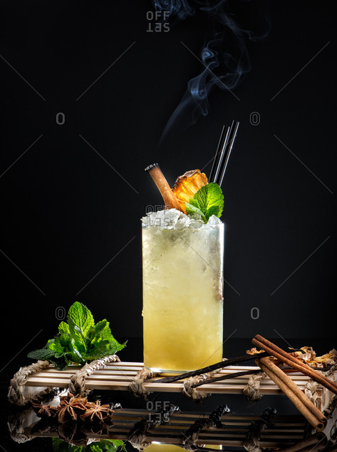 Glass of yellow spicy alcoholic drink garnished with fresh mint leaf and smoking cinnamon stick against black background