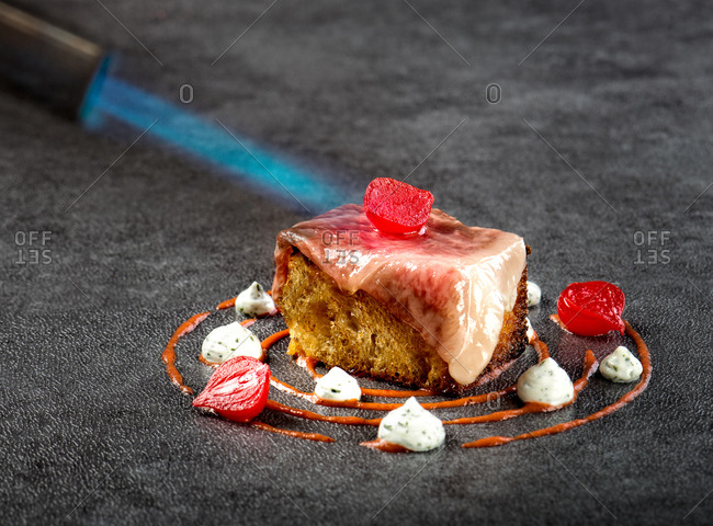 Closeup of sophisticated Turkish dish made with wagyu beef fillet served on piece of pastry and garnished with chili cream sauce and yogurt with marinated onion being grilled with torch burner