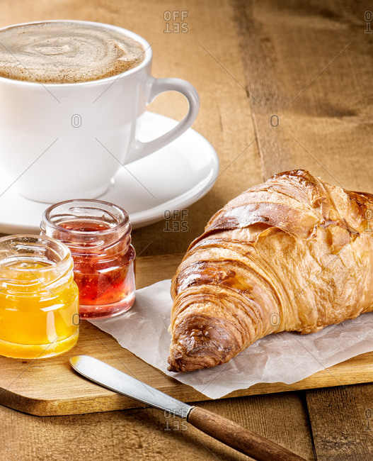Delicious freshly baked croissant served with fruit marmalade and cup of hot coffee with milk on wooden table