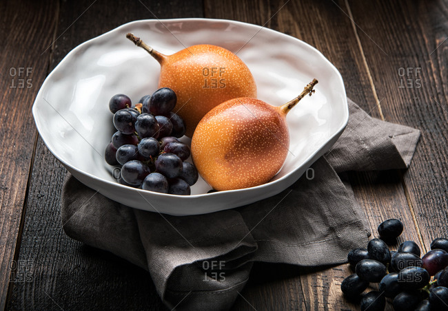 Ripe passion fruits and bunches of purple grapes placed on wooden table in kitchen